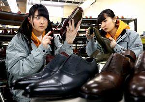 紳士靴の塗装作業をする木本花音さん(左)と内山命さん=細川卓撮影