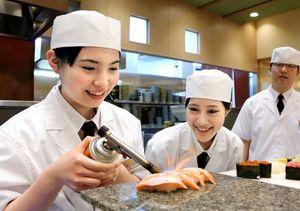 自ら握ったサーモンの握り寿司をバーナーであぶる松本梨奈さん(左)と高木由麻奈さん=細川卓撮影