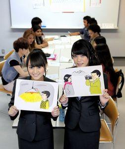教材のボードを持って笑顔を見せる犬塚あさなさん(左)と酒井萌衣さん=名古屋市中区、高橋雄大撮影