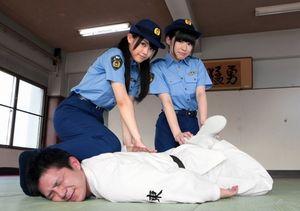 逮捕術を体験する竹内舞さん(左)と岩永亞美(つぐみ)さん=名古屋市東区、高橋雄大撮影