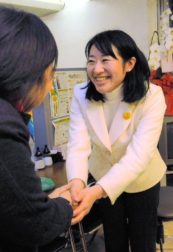 写真:支持者と握手を交わす越直美氏(右)=大津市木下町