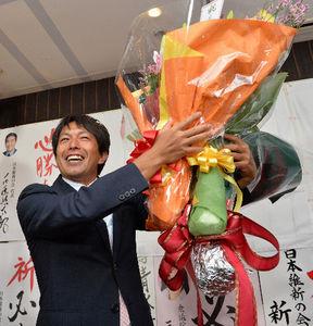 写真:当選を決め、花束を手に喜ぶ清水貴之氏=西宮市