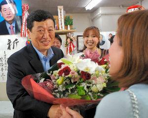 写真:支持者から花束を受け取る柳本卓治さん=大阪市西成区