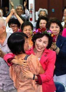 写真:当選を決め、娘と抱き合って喜ぶ糸数慶子氏=21日午後9時38分、那覇市、藤脇正真撮影
