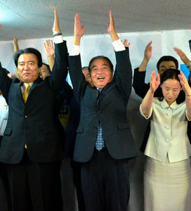 写真:当選確実の報を受けて万歳する平野達男氏=盛岡市中央通1丁目の選挙事務所