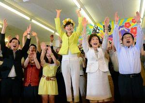 写真:当選を決め、支持者と万歳をする佐々木さやか氏=横浜市中区