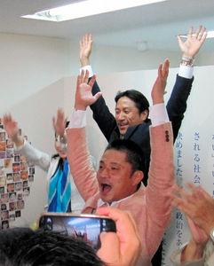 写真:当選確実となり、万歳する川田龍平氏(奥)=21日午後8時23分、東京都世田谷区