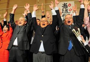 写真:4選を決め、万歳をする武見敬三氏(中央)=21日午後11時47分、港区、吉永岳央撮影