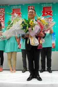写真:再選を決め、花束を手にする長浜博行氏=千葉市中央区