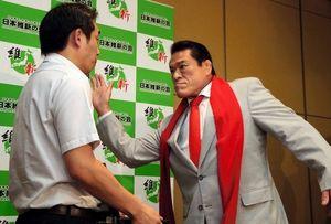 写真:会見に出席した記者に気合を入れる日本維新の会のアントニオ猪木氏=21日午後10時28分、東京都港区、上田潤撮影