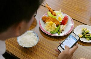 写真:遊説の合間、食事をとりながらスマートフォンでツイッターをチェックする候補者=4日正午、大阪市内、竹花徹朗撮影