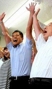 写真:支持者らと万歳する辰巳孝太郎さん(中)=大阪市中央区