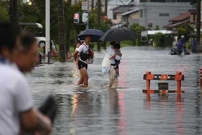 台風18号接近に伴う大雨で避難勧告が出た静岡県浜松市南区では、冠水した道を子どもを背負って歩く住民の姿が見られた=9月8日午後5時25分