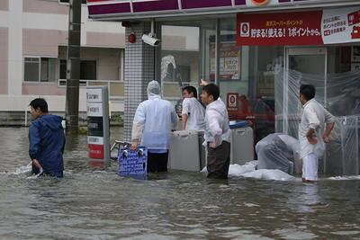浸水した店舗の前で片付けをするコンビニの店員ら=9月8日午後5時32分、静岡県浜松市南区
