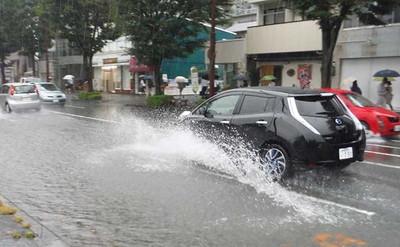 大雨で水があふれた道路を走る車=8日午前8時40分、浜松市中区常盤町