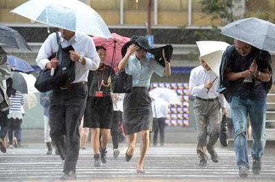 激しく雨が降る中、横断歩道を渡る人たち=9月9日午後4時24分、JR東京駅前