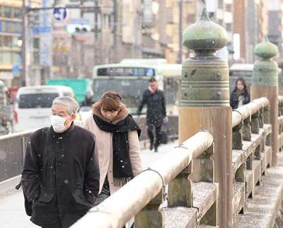 小雪が舞う中、厚着をして三条大橋を歩く人たち=6日午前7時36分、京都市中京区、戸村登撮影
