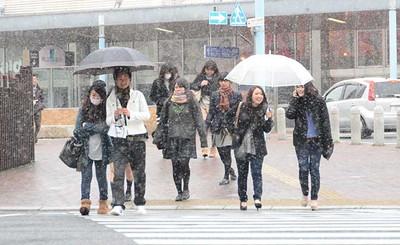 雪の中、マフラーや帽子などを身につけ、傘を差して歩く人たち=JR岡山駅前