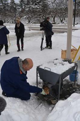 薪ストーブを使った融雪実験をする青森県弘前市職員=弘前市役所