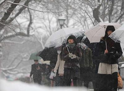 雪の中、大学入試会場に向かう受験生ら=8日午前、東京都千代田区