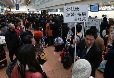欠航が相次ぎ、航空会社のカウンターは、払い戻しなどを求める乗客であふれた=8日午前、羽田空港