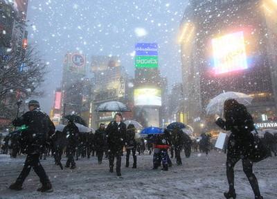 雪の中、JR渋谷駅前のスクランブル交差点では、電光掲示板がかすんで見えた=8日午後、東京都渋谷区