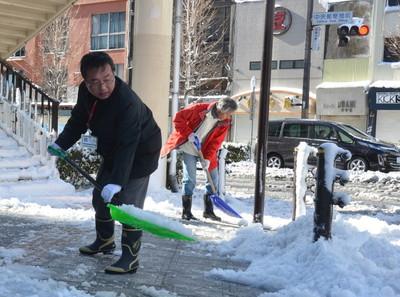 歩道で雪かきをする人たち=9日午前9時25分、水戸市三の丸1丁目