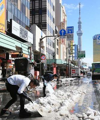 雪かきをする人力車の車夫ら=9日、東京都台東区
