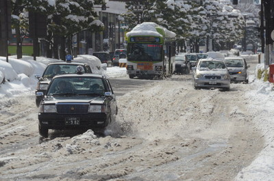 道路は解けた雪と水でぬかるみのようになった=9日午前10時44分、甲府市丸の内1丁目