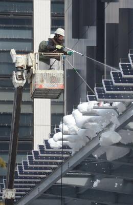 甲府市役所のソーラーパネルに着いた雪に水をかけて落とす作業員=9日午前11時10分、甲府市丸の内1丁目