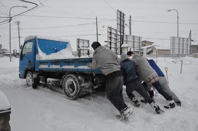 大雪で立ち往生し、集まった近所の人たちに押してもらうトラック=宮城県東松島市大曲