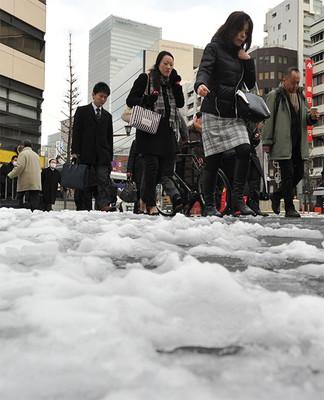 路面が凍結した交差点で、足元に気をつけながら通勤する人たち=10日午前、東京都中央区