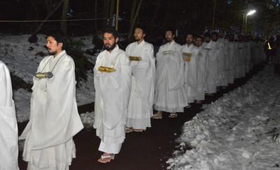 荒行を終えて雪の残る境内を歩く僧侶ら=市川市の中山法華経寺