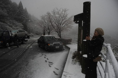 珍しい雪を写真に収める人=日南市北郷町北河内の飫肥杉展望台(一部画像を加工しています)