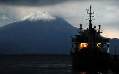 冠雪した桜島=鹿児島県姶良市の加治木港