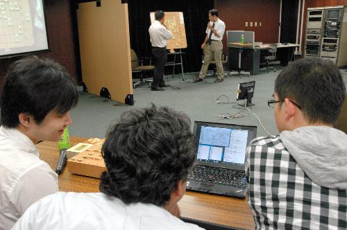 写真:大盤の前で指し手を話し合う対局者を遠目にパソコンはフル稼働=7月24日午後、東京都調布市の電気通信大学