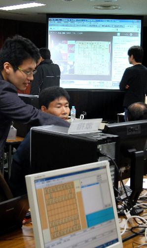 写真:対局の進行は会場のパソコン画面とスクリーンに映し出された=東京都調布市