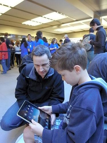 写真:ニューヨークのアップルの店舗で買ったばかりのiPadを試す親子=4月3日