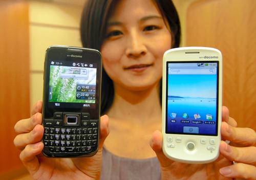 写真:グーグルのOS「アンドロイド」搭載の携帯端末(右)とマイクロソフトの新OSを搭載した端末(左)