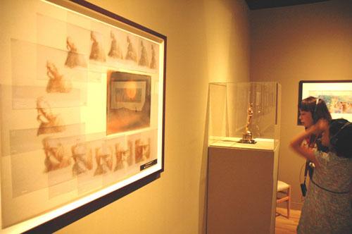 写真:展覧会会場に展示されている「木を植えた男」の原画。奥にはオスカー像=東京都現代美術館