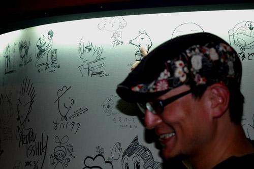 写真:来館記念に西尾さんが描いたオシイヌ(壁の中央上端)。オシイヌとは押井守監督をイヌ化したキャラクター