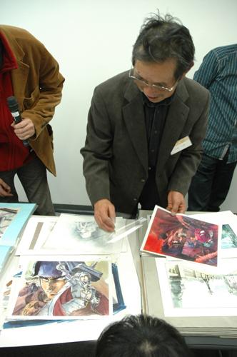 写真:「剣風伝奇ベルセルク」のイラストを手に話す小林さん