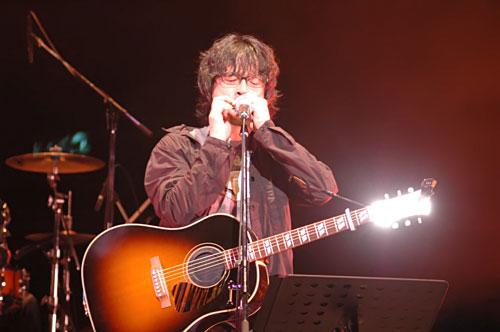 写真:ブルースハープを吹く浦沢さん