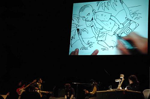 写真:バンドの即興演奏を聞き即興で絵を描く浦沢さん(右下)