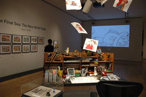 写真:尾田さんの仕事机の再現と原画が展示されている