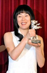 銀熊賞のトロフィーを手に笑顔 ...