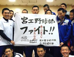 写真:コブクロから贈られた旗を掲げる宮崎工の選手たち=大阪市北区