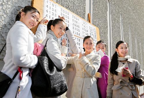 写真:宝塚音楽学校に合格し、掲示板の前で記念撮影をする受験生ら=29日午前、兵庫県宝塚市、諫山卓弥撮影
