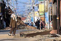 壊れた自宅の前で片付けをする女性=16日午前7時、熊本県益城町、内田光撮影