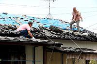 雨に備えて屋根にブルーシートをかぶせる人たち=16日午後2時30分、熊本県益城町、内田光撮影